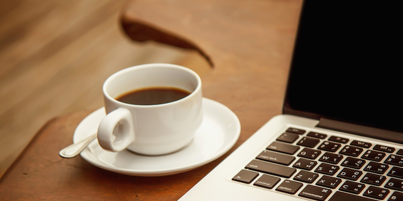 Black coffee in a white cup on a table with a computer.